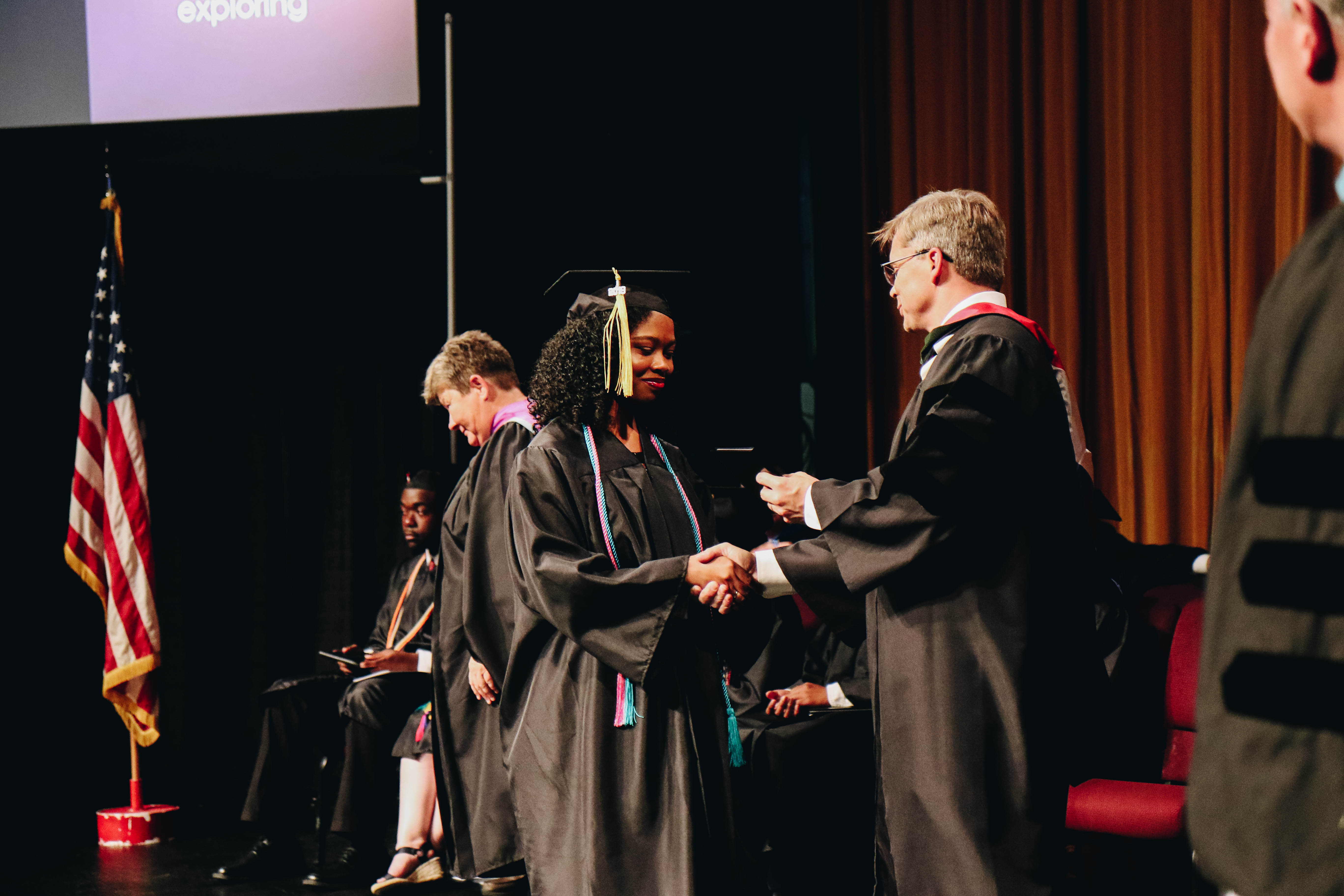 Female Morris student walking across stage at graduation
